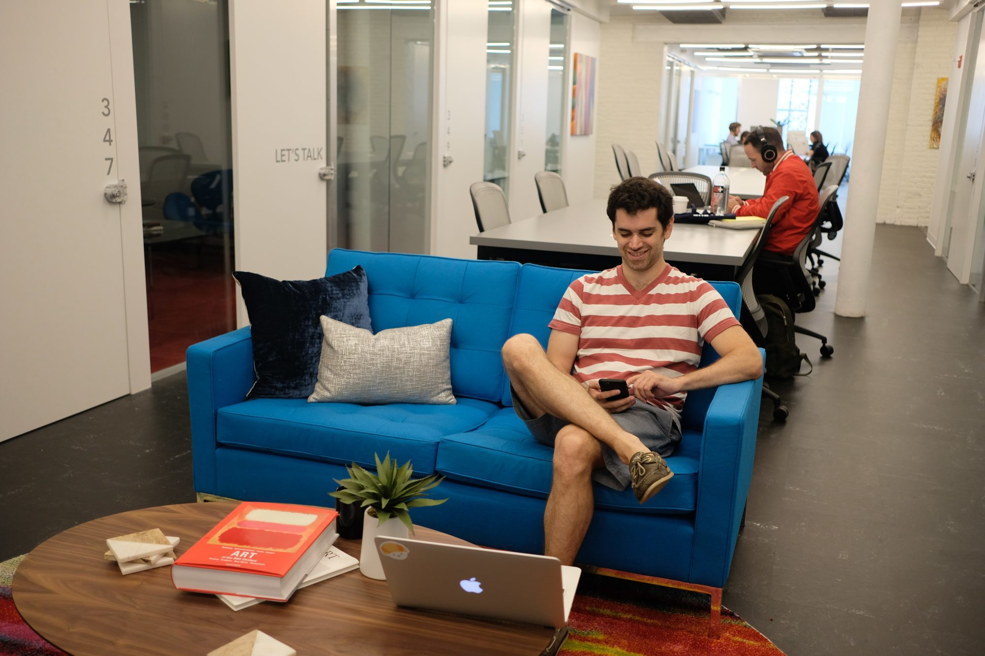 man sitting on blue couch in coworking space