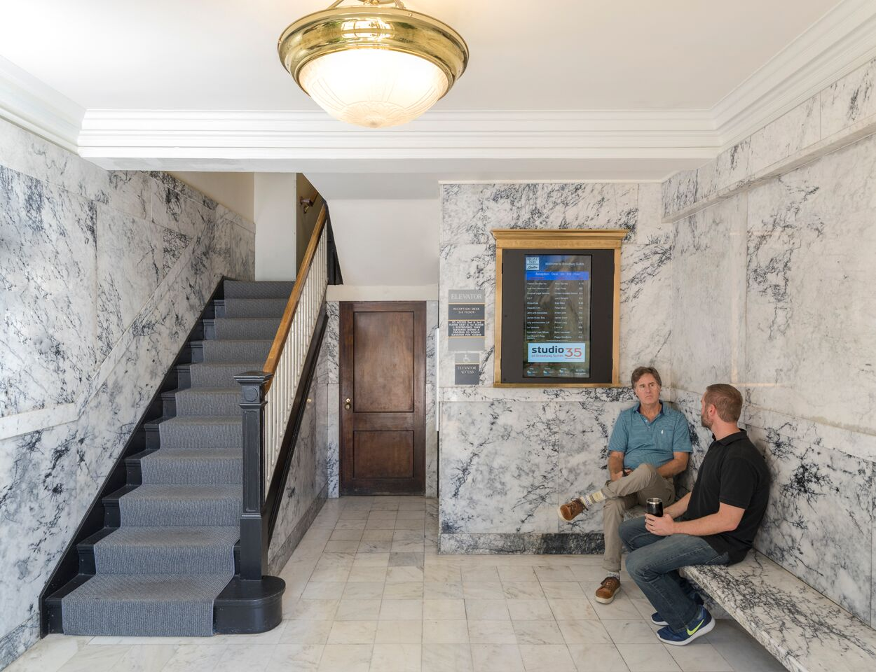 two men talking on bench in building lobby